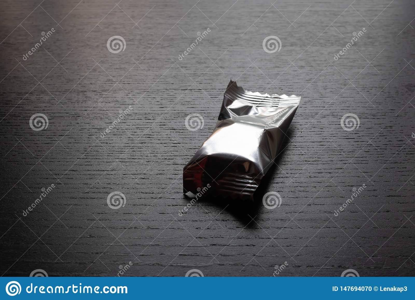 Candy si è avvolto nella borsa del pacchetto della stagnola d argento sulla tavola nera - immagine