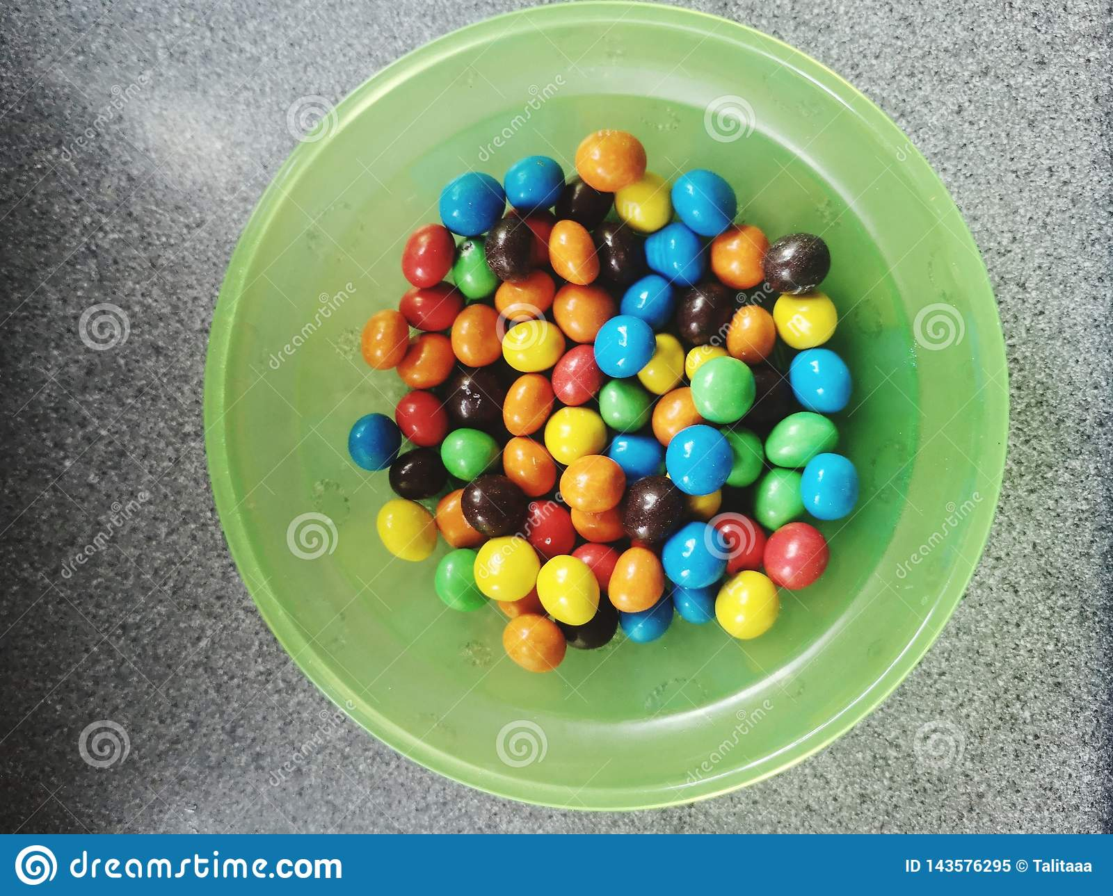 The candy ,  I love them , colored sweets in a green bowl on the table