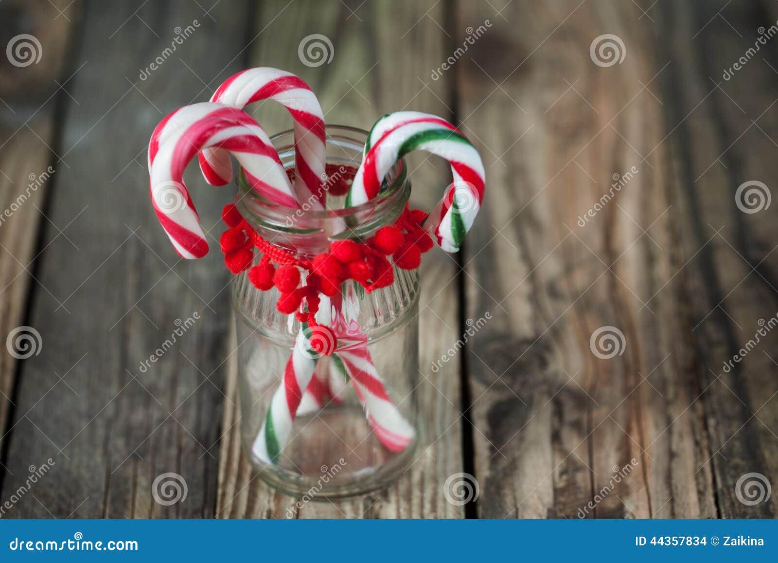 Candys dolci di Natale nel vetro sui precedenti di legno
