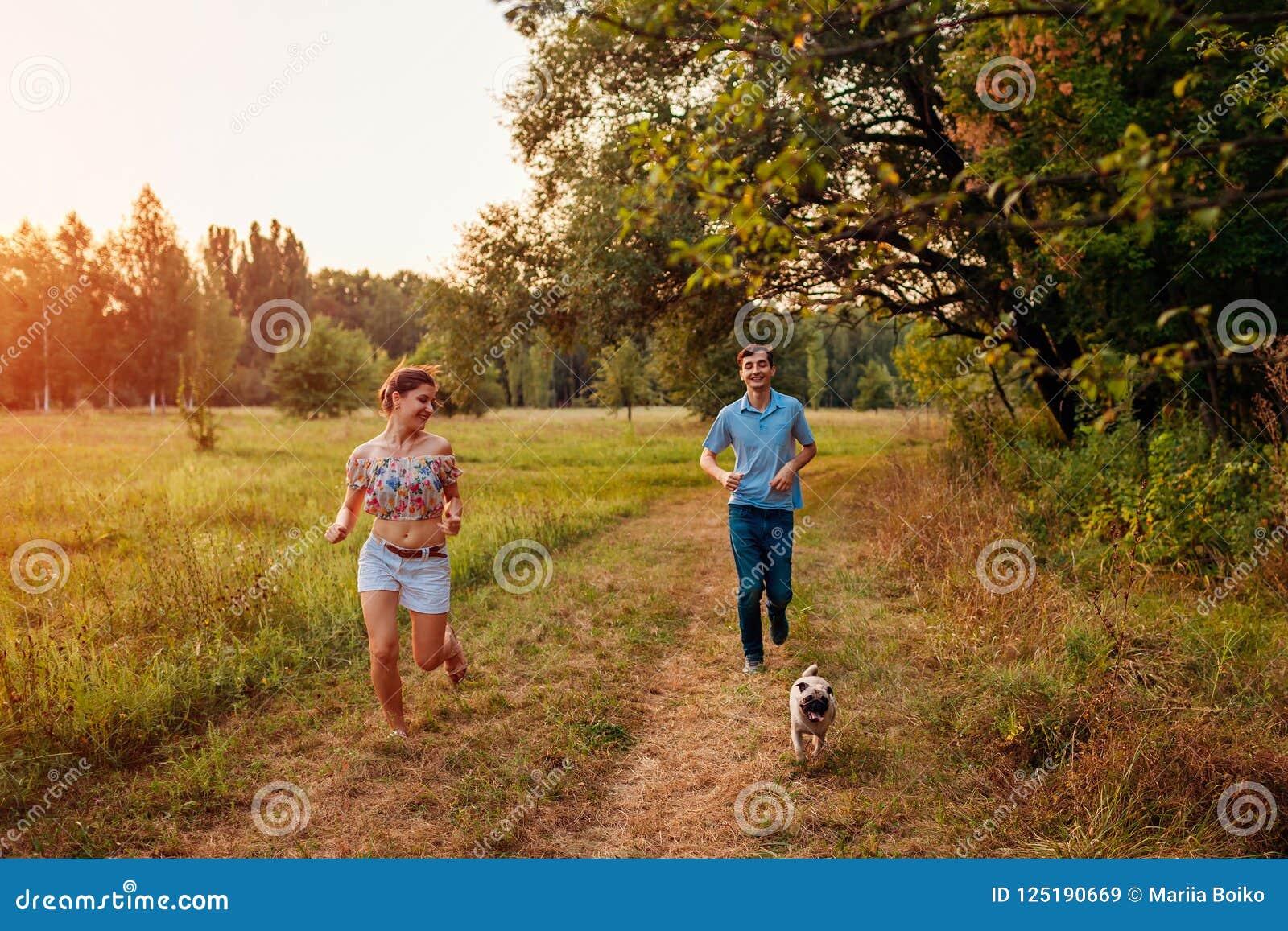 Cane di camminata del carlino delle giovani coppie nel funzionamento felice del cucciolo della foresta di autunno avanti e divert