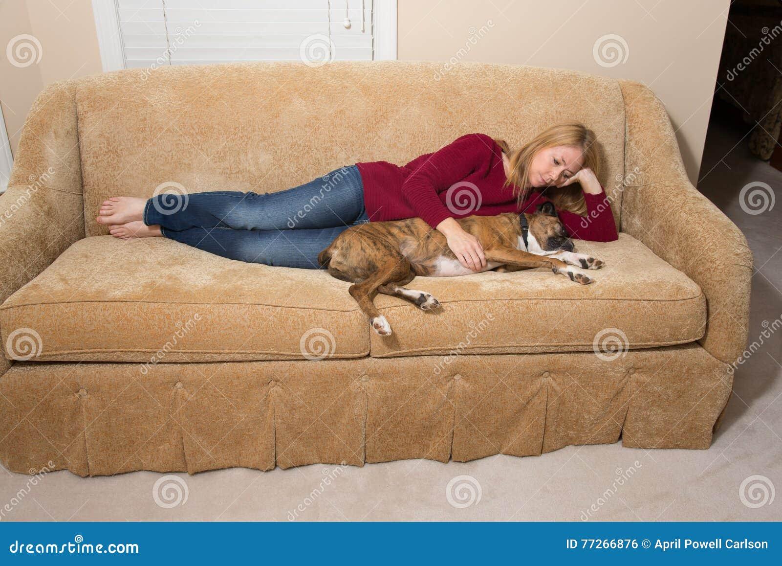 Cane di coccole della donna sullo strato - il cane è addormentato