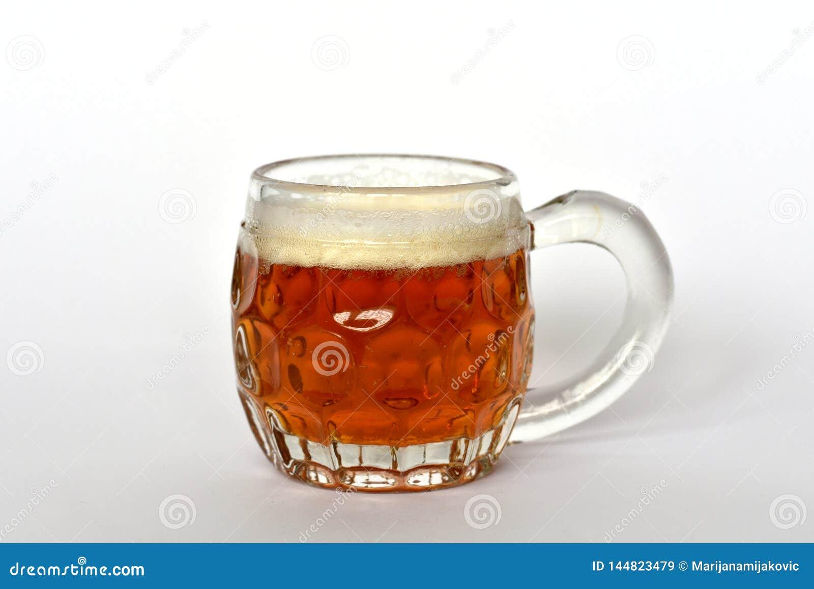Caneca de vidro com punho completamente da cerveja dourada do ofício