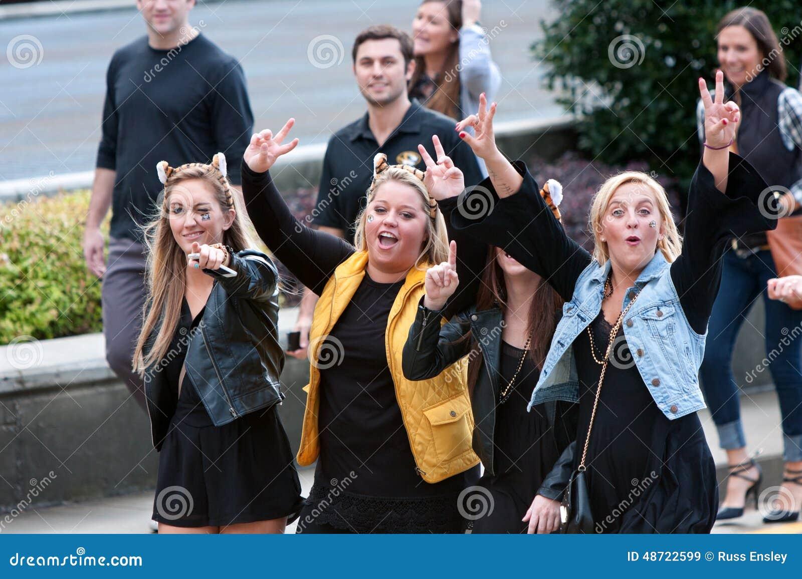 Caneca fêmea entusiasmado dos fan de futebol da faculdade para a câmera