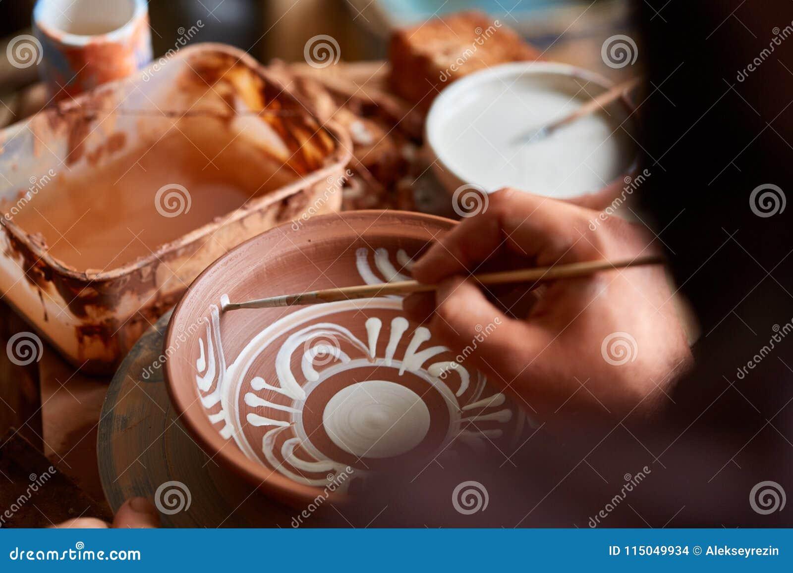Caneca feito a mão semelhante em uma prateleira de madeira, close-up do oleiro da cara assustador, profundidade do shellow do cam