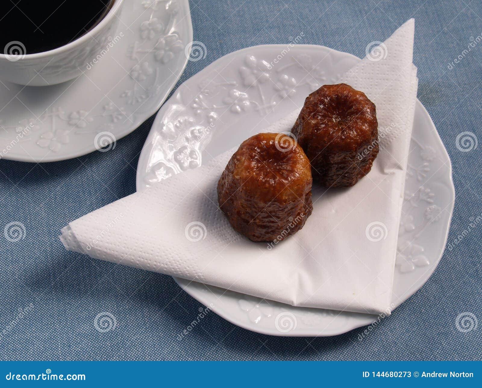 Canelé français traditionnel de gâteaux avec du café