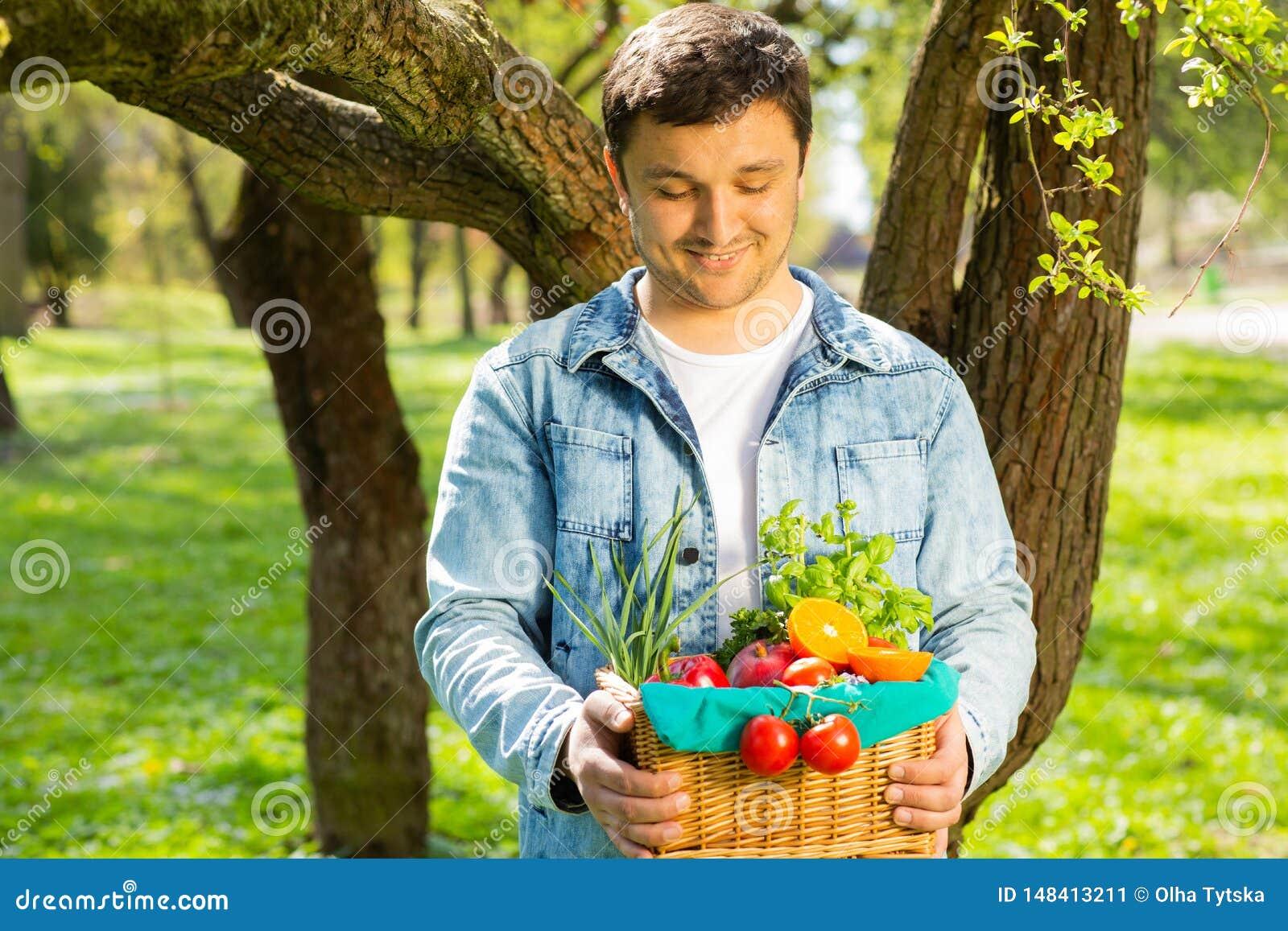 Canestro con le verdure e frutti nelle mani di un fondo dell agricoltore della natura Concetto dello stile di vita sano