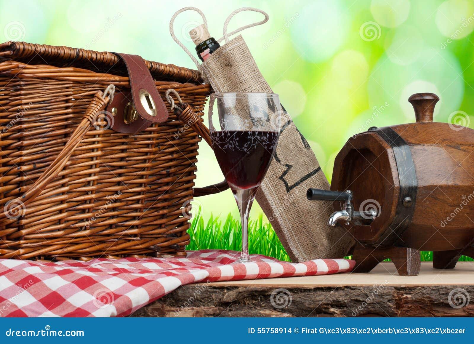 Canestro di picnic sulla tavola con bicchiere di vino e la botte