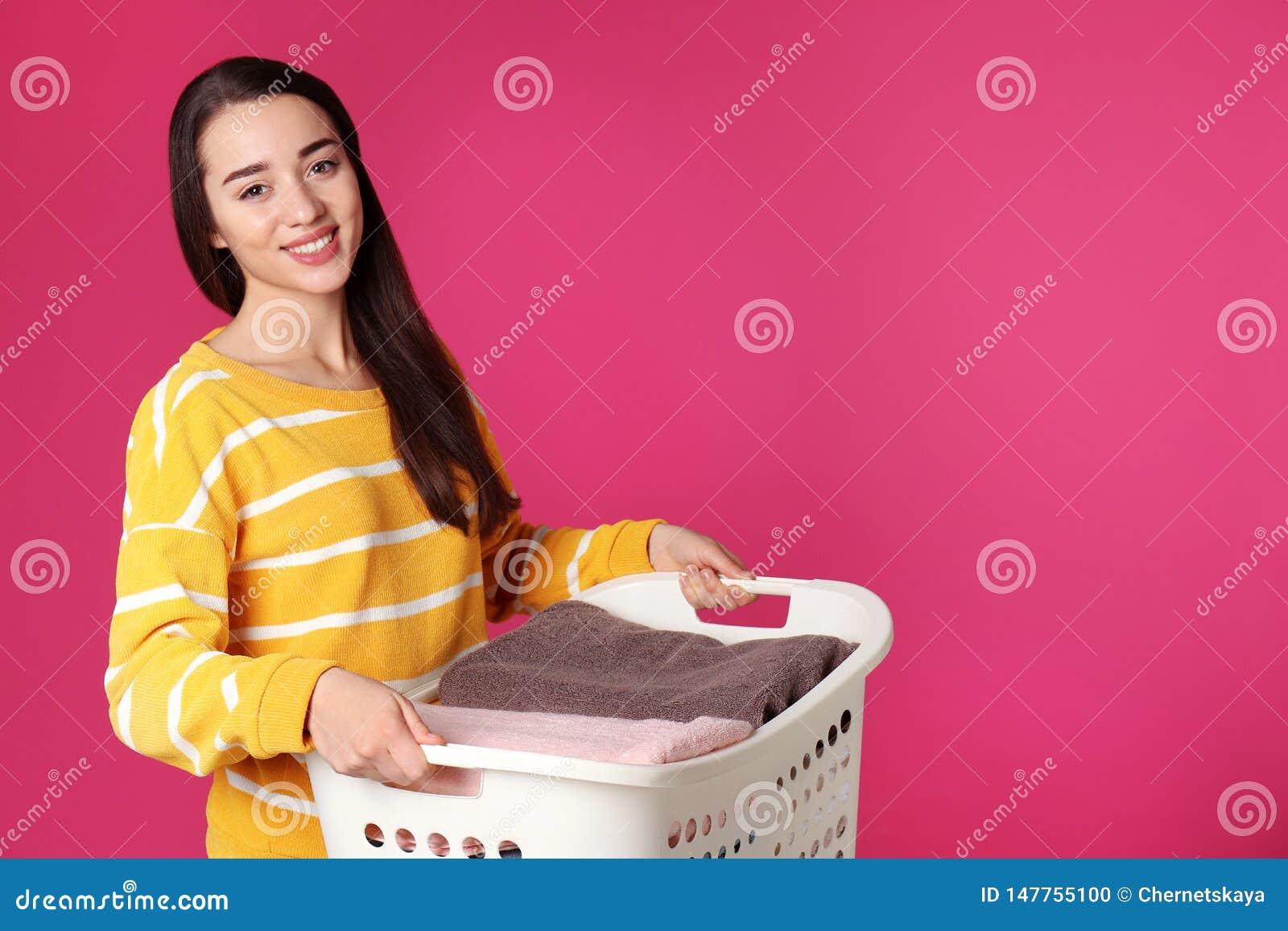 Canestro felice della tenuta della giovane donna con la lavanderia sul fondo di colore