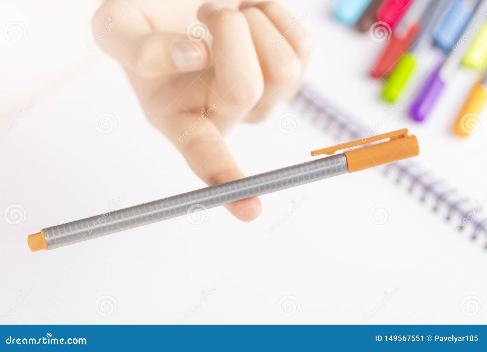 Caneta com ponta de feltro alaranjada no equilíbrio no dedo de uma criança