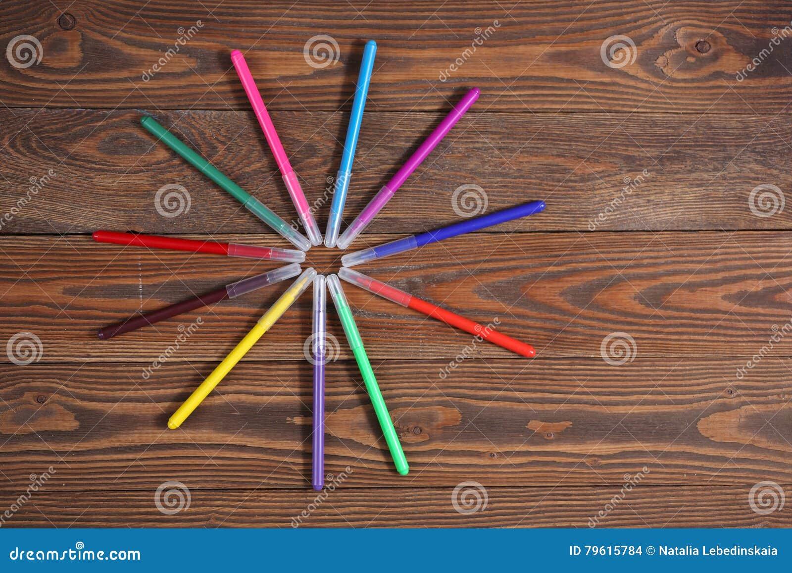 Canetas com ponta de feltro coloridas em um fundo de madeira da tabela, o conceito