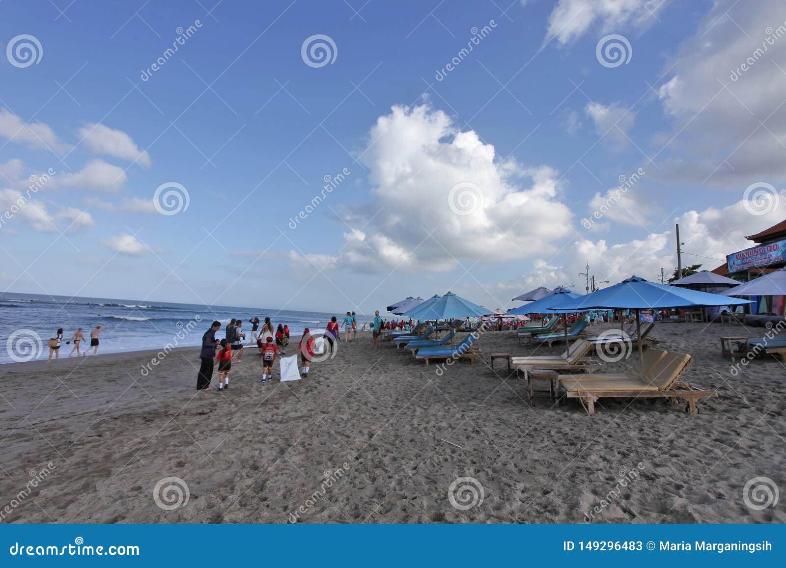 Canggu, Indonesia - 27 maggio 2019: Il giorno soleggiato godente turistico nella spiaggia e gli studenti locali uniscono l attivi