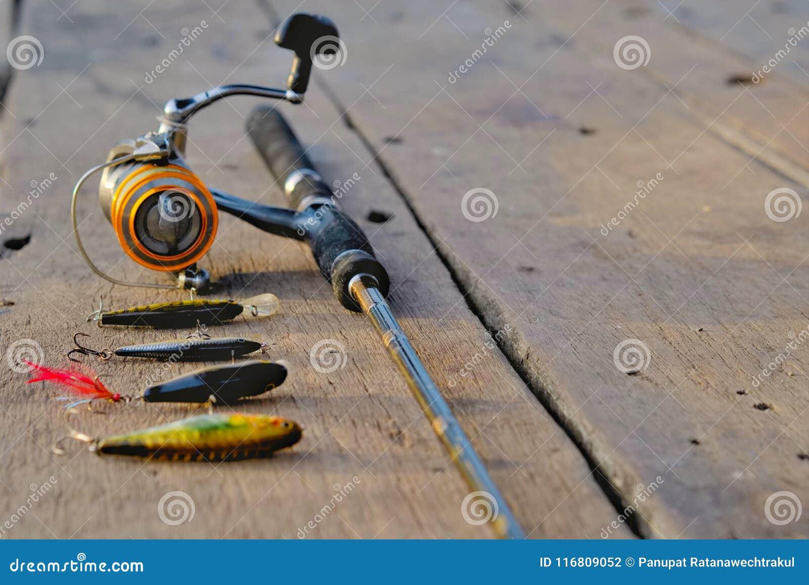 Canna da pesca ed esca di pesca sulla tavola di legno