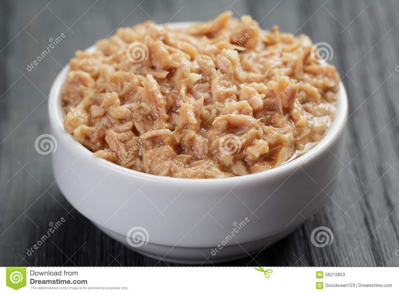 Canned tuna in white bowl on wood table