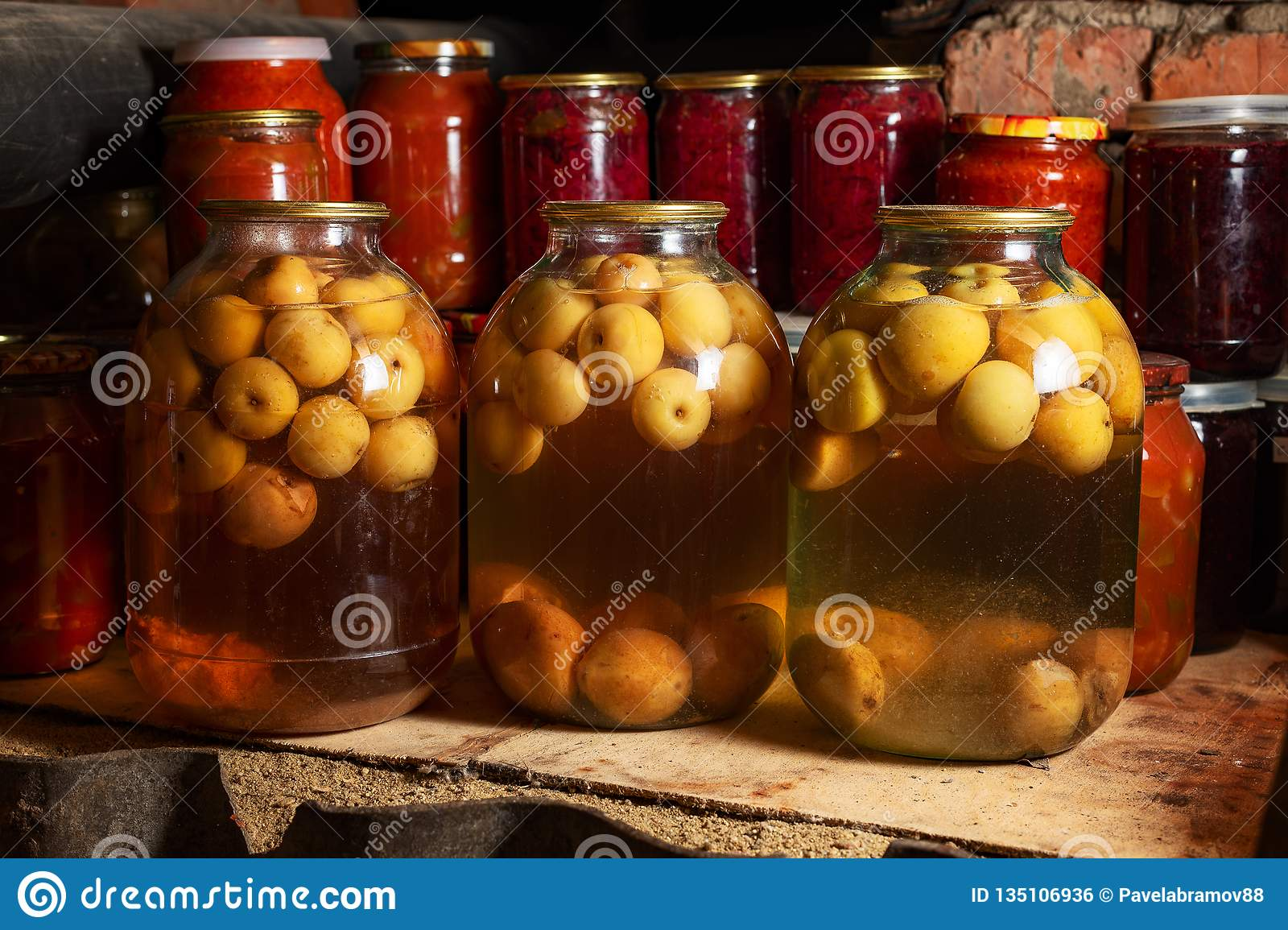 Canned vegetables in transparent glass jar. Apple compote in large transparent jars. Homemade canned juice