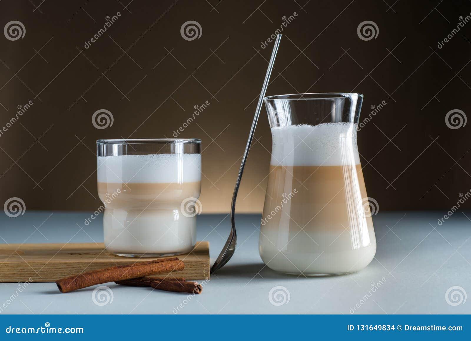 Cannella di vetro moderna delle tazze del caffè del Latte su fondo scuro marrone blu