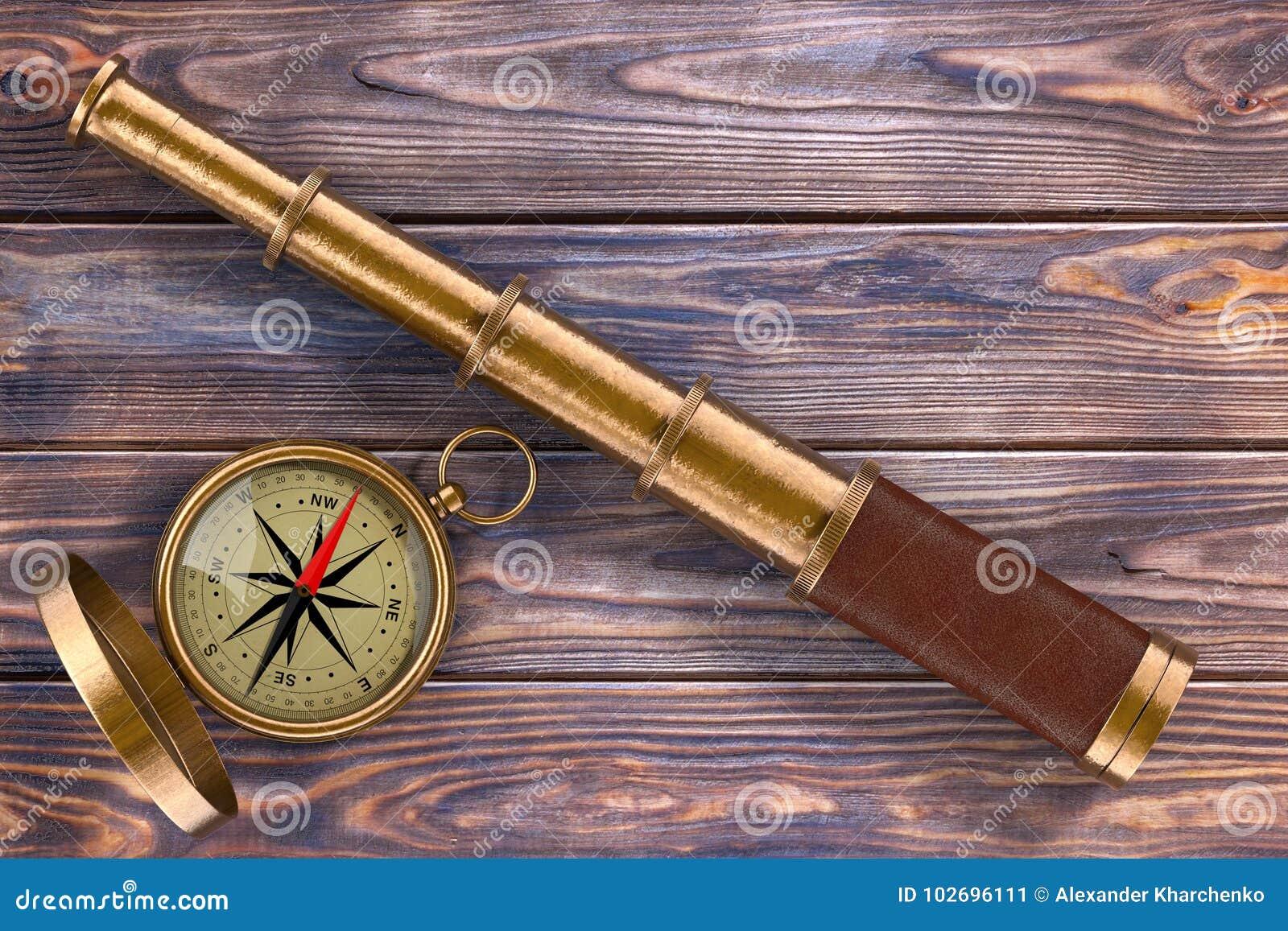 Cannocchiale d annata dorato del telescopio con la bussola sopra la Tabella di legno