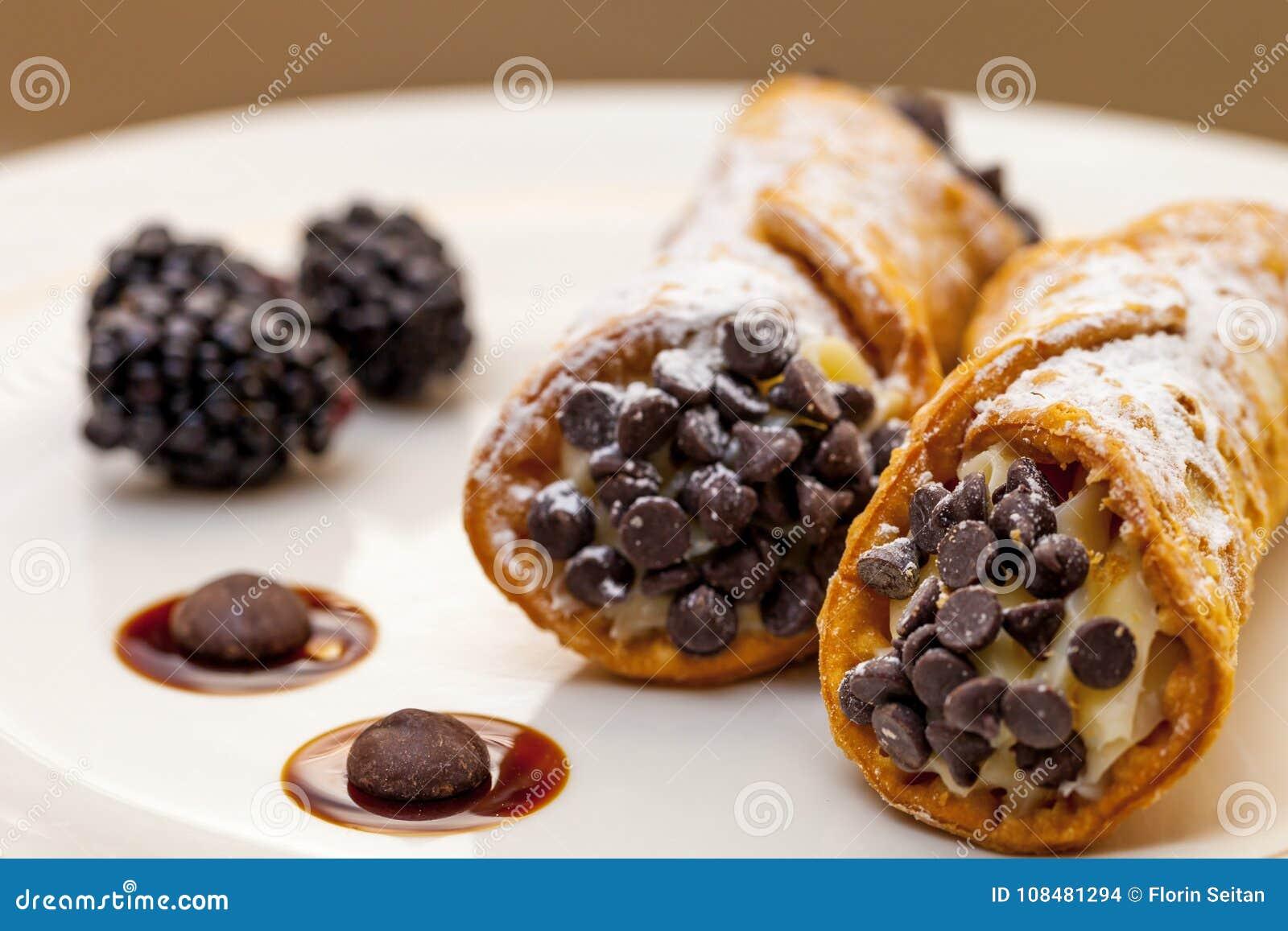 Cannoli italiano na placa branca com amoras-pretas e pedaços de chocolate