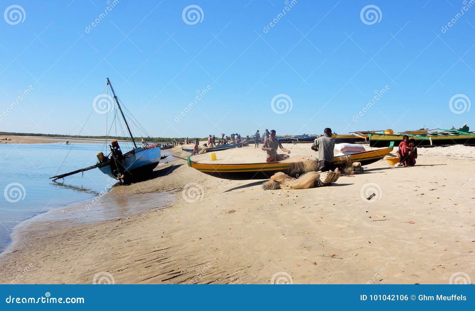Canoës malgaches sur la plage avec les pêcheurs travaillants