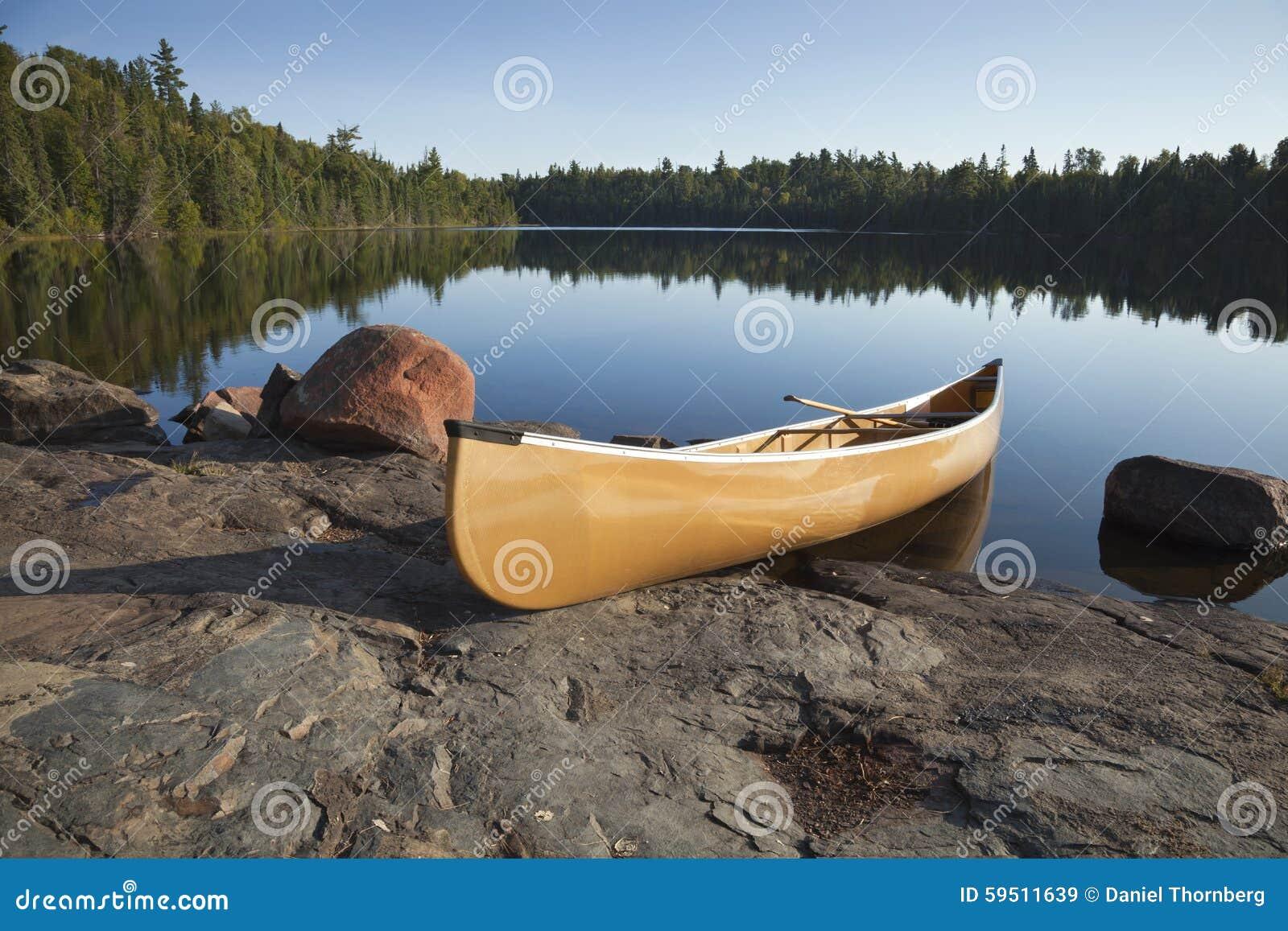 Canoa amarela na costa rochosa do lago calmo com pinheiros