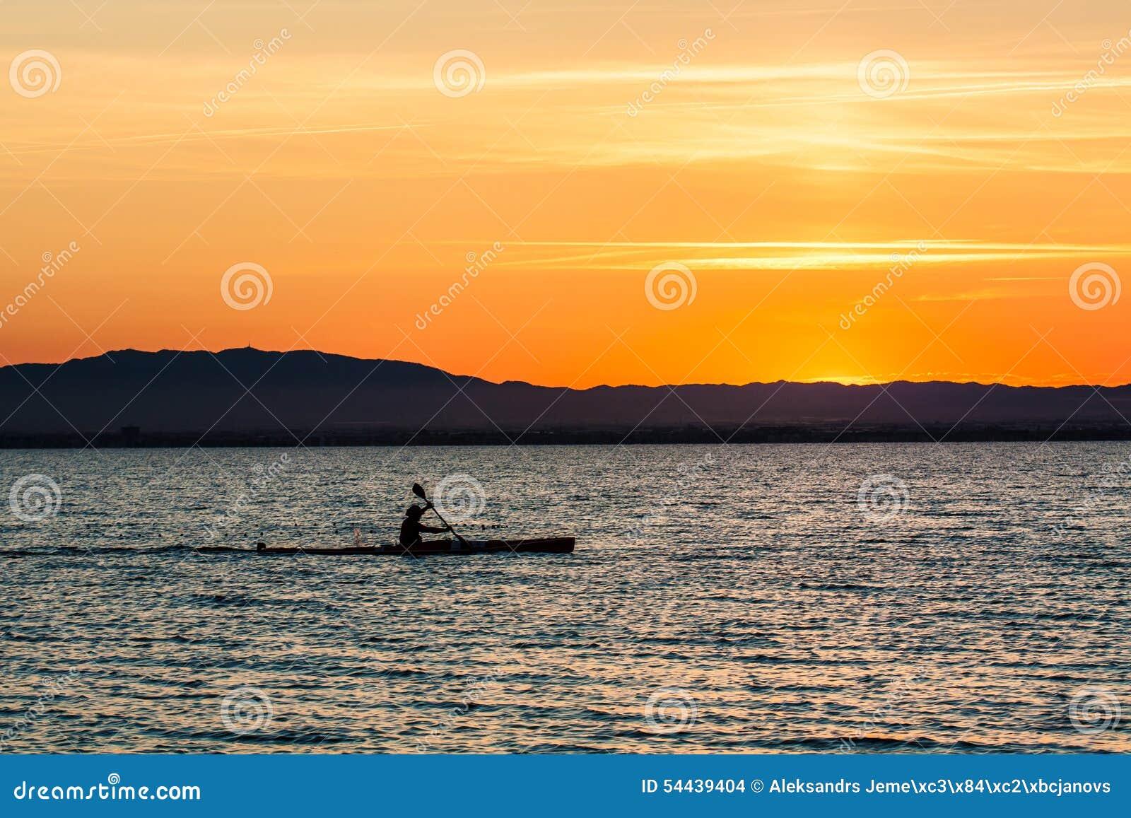 Canoa dell uomo sul tramonto