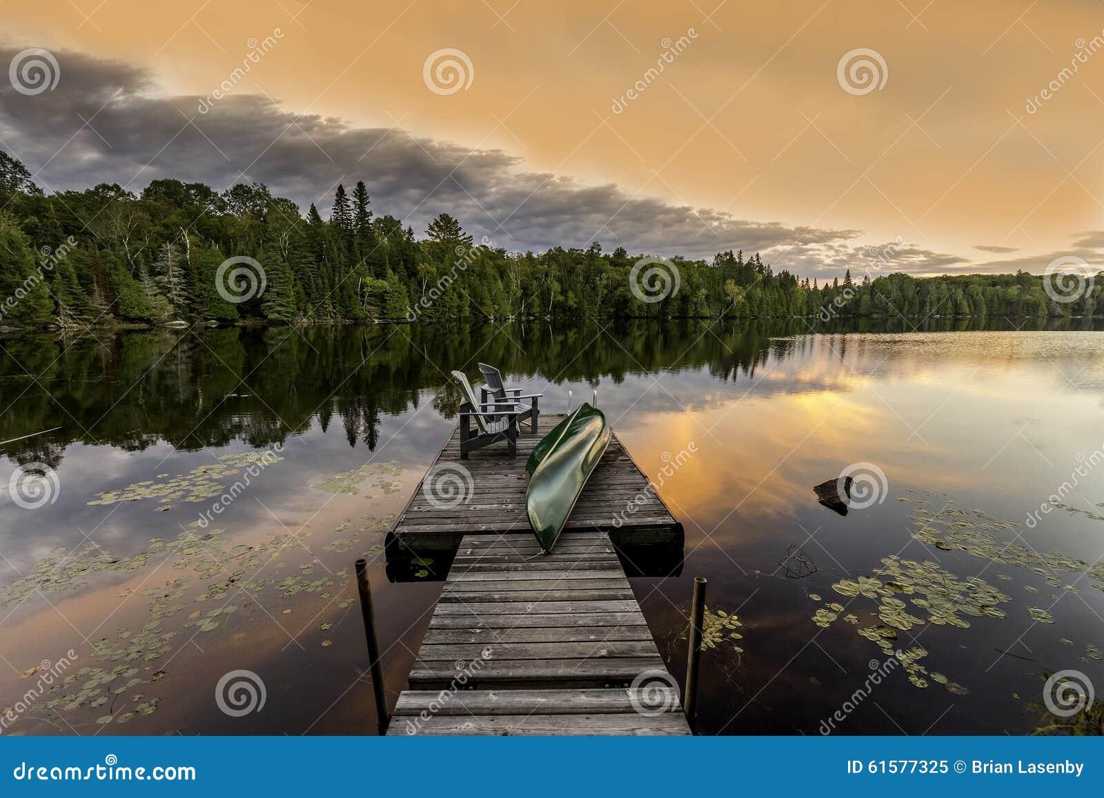 Canoa y sillas verdes en un muelle en la puesta del sol