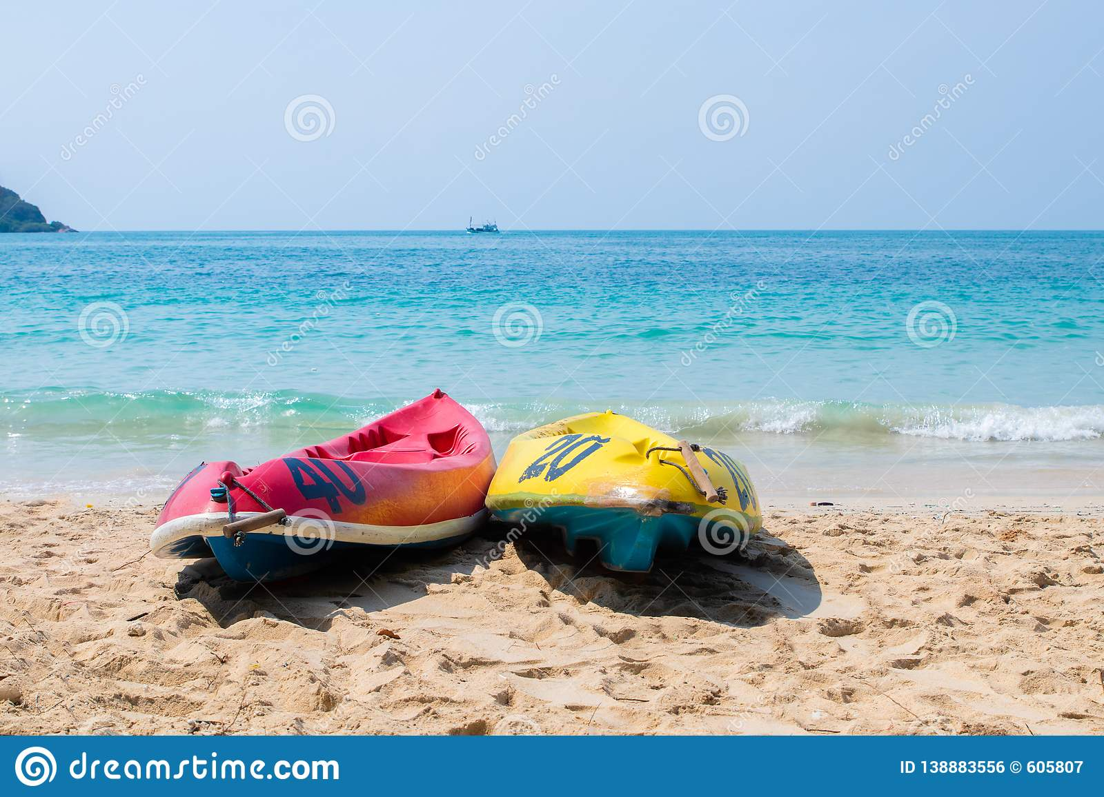 c45e4afbbc8 Yellow and blue kayaks on the beach on a sunny day. Sports summer hobby