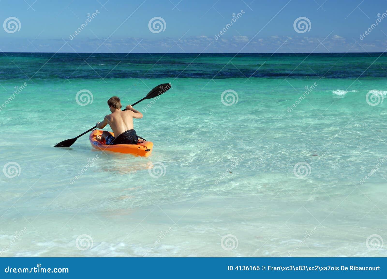 Canoeist de solo que rema no mar