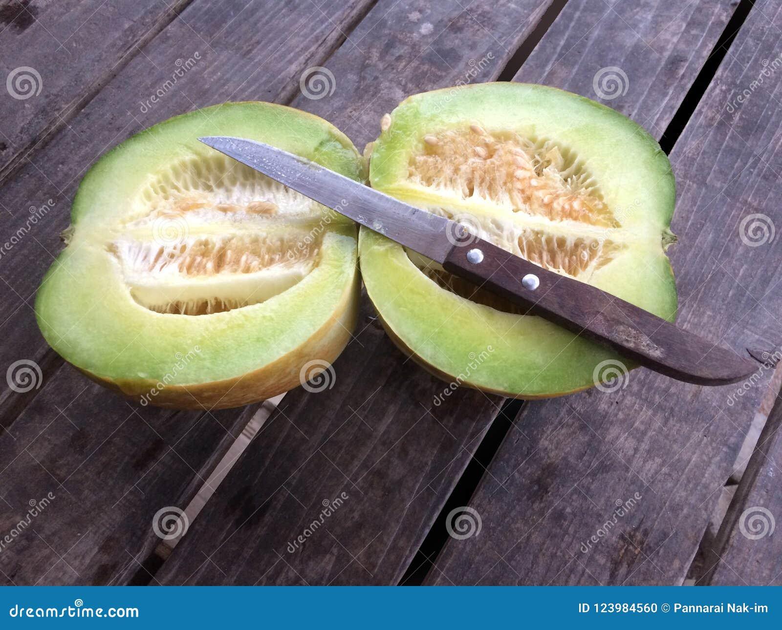 Cantaloupmelon eller muskmelon och kniv på den gamla trätabellen