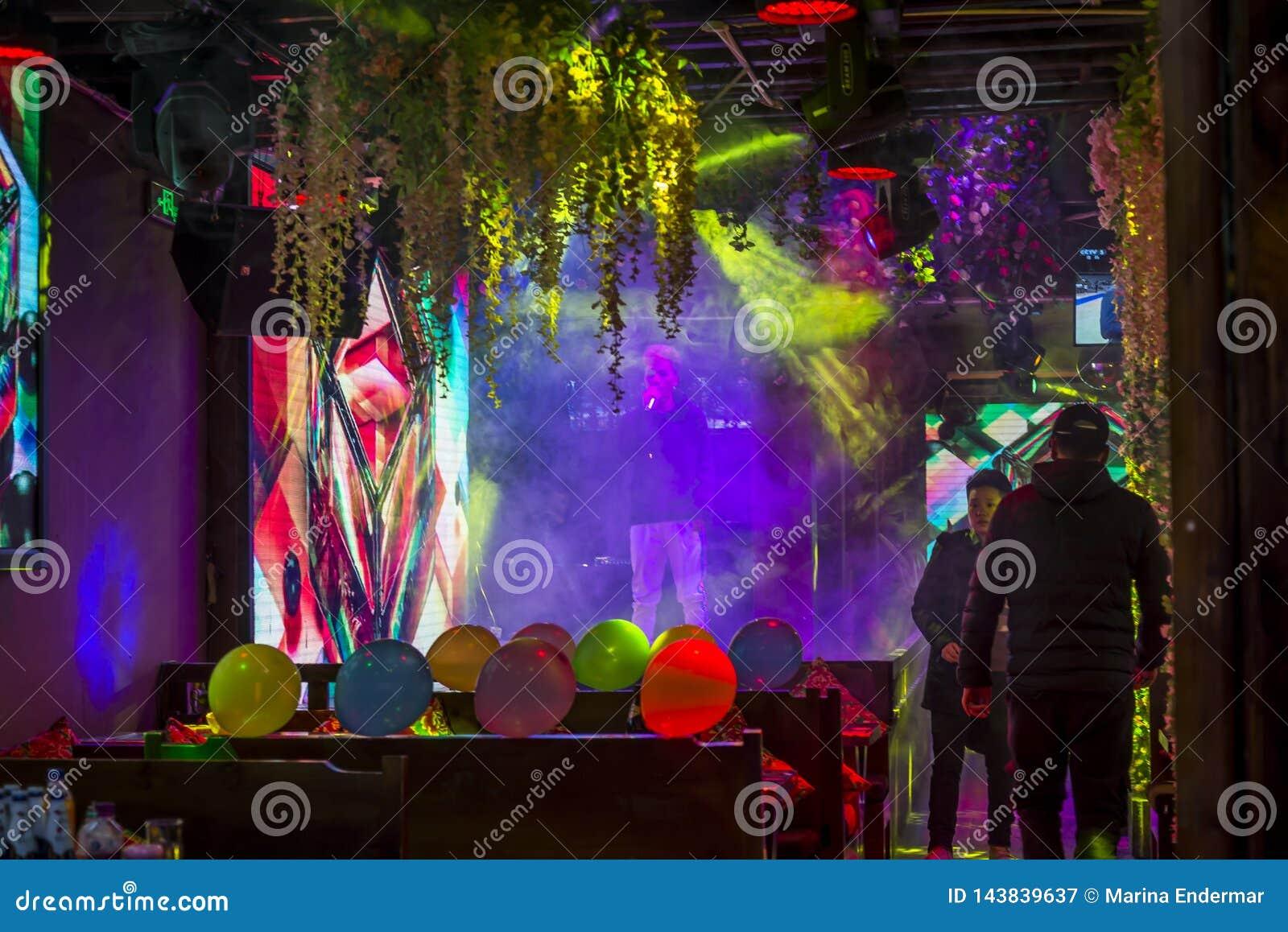 Cantante che canta in una barra colourfully decorata, Dali, Cina