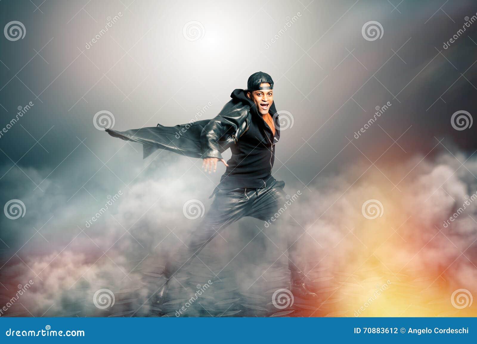Cantante de roca de sexo masculino con el cabo en paisaje misterioso con humo