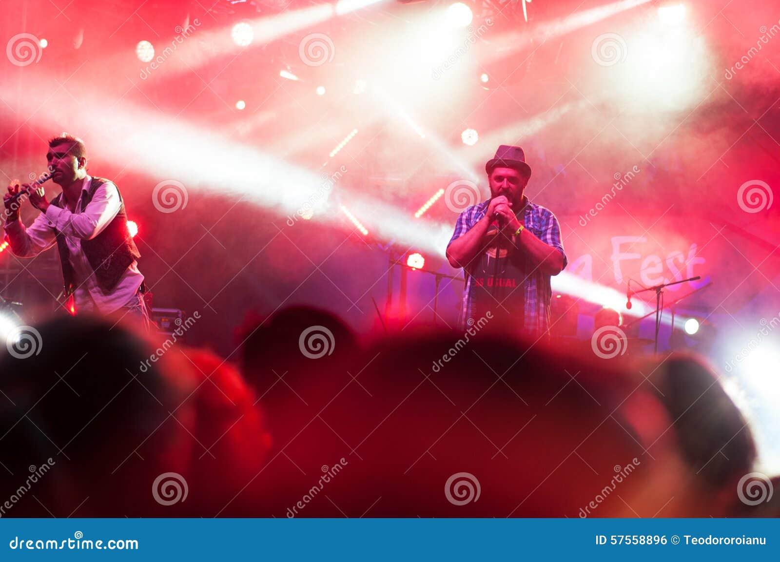 Cantante nellilluminazione di concerto fotografia editoriale