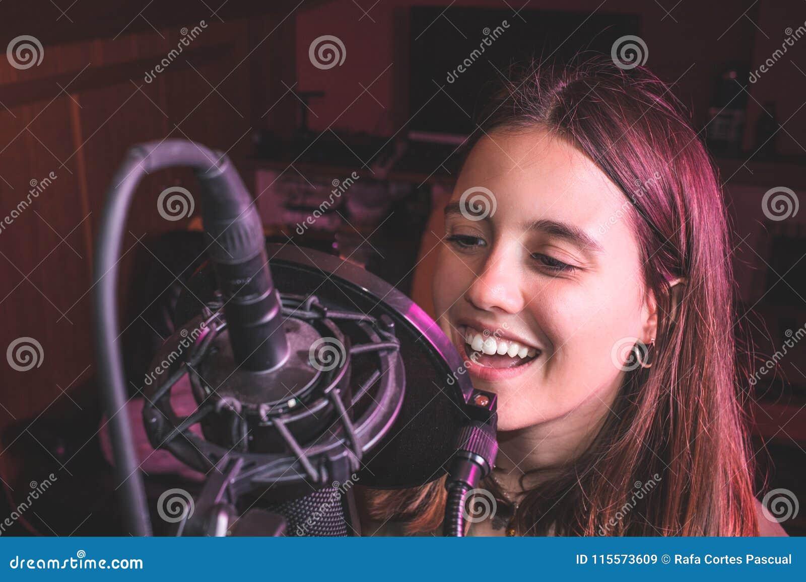 Canto della ragazza di canto con un microfono