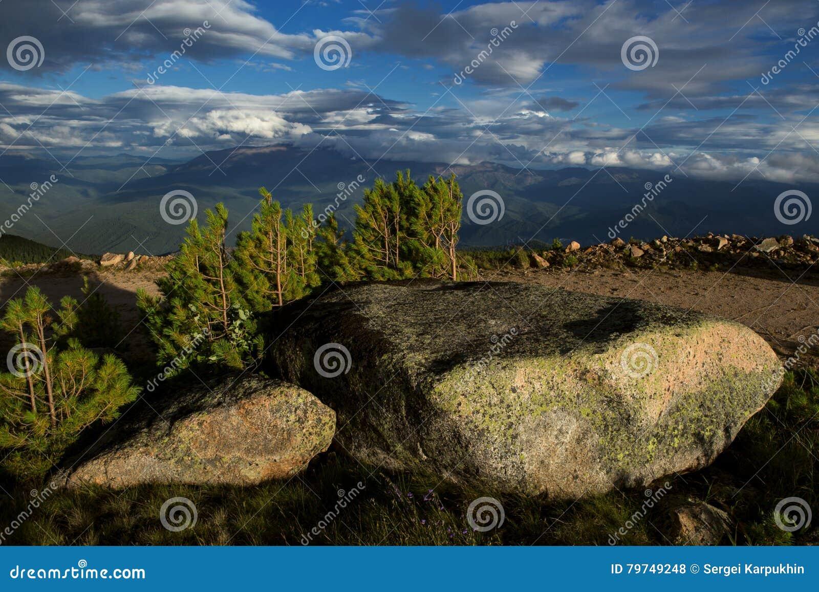 Cantos rodados y nubes grandes del granito sobre un valle de la montaña