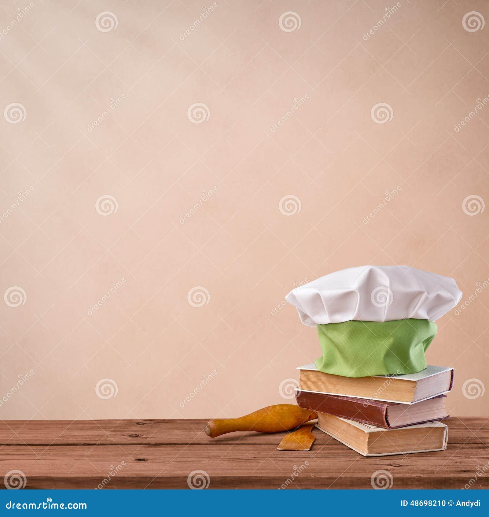 Cap chef, cookbook and kitchenware on beige vintage texture background ...