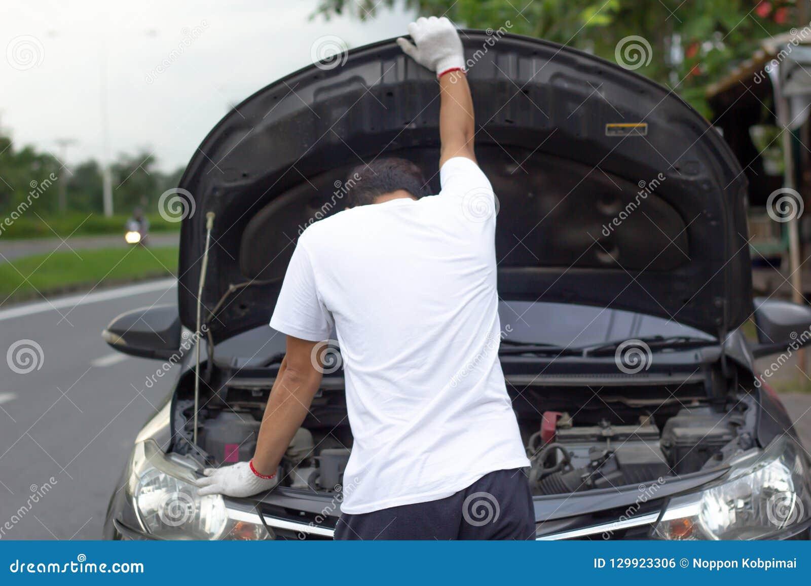 Capa aberta vestindo do carro das luvas do mecânico que verifica o wh do óleo do motor de automóveis