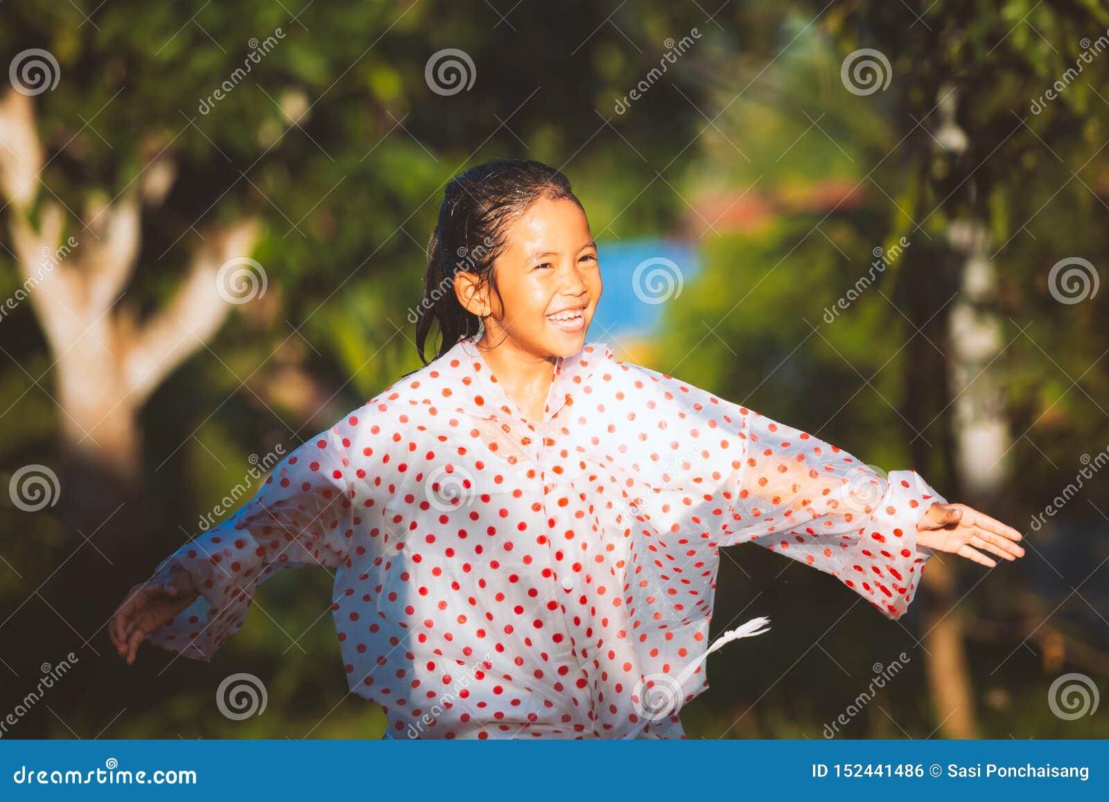 Capa de chuva vestindo da menina asiática da criança que tem o divertimento a jogar com a chuva na luz solar