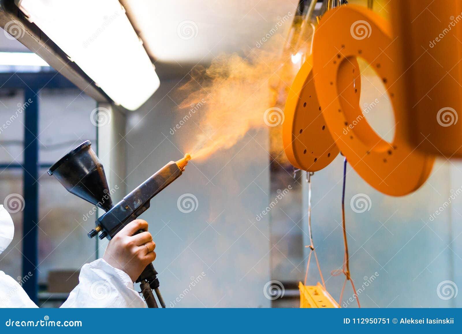 Capa del polvo de piezas de metal Una mujer en un traje protector rocía la pintura del polvo de un arma en productos de metal
