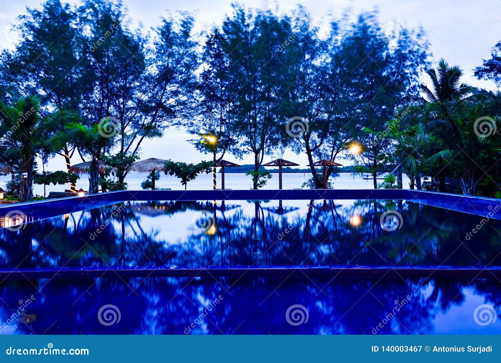 Capanne tradizionali di rilassamento sulla spiaggia con la piscina blu nell alba fresca di mattina