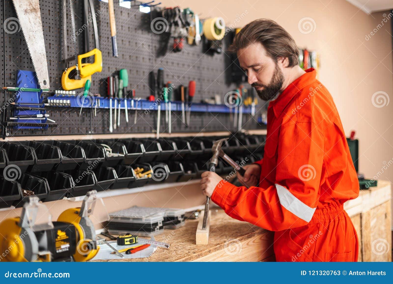6f9a49716fe Capataz en ropa de trabajo anaranjada cuidadosamente usando el martillo con  el soporte de diversas herramientas cerca en taller