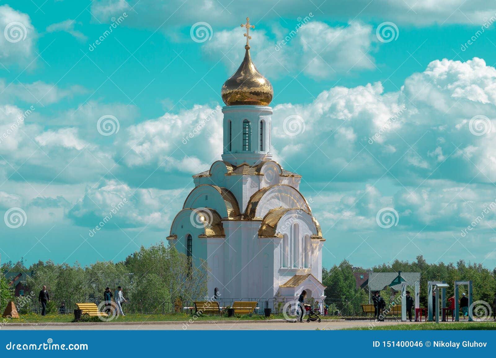 Capela da igreja ortodoxa do russo em um fundo do céu cor-de-rosa com nuvens brancas