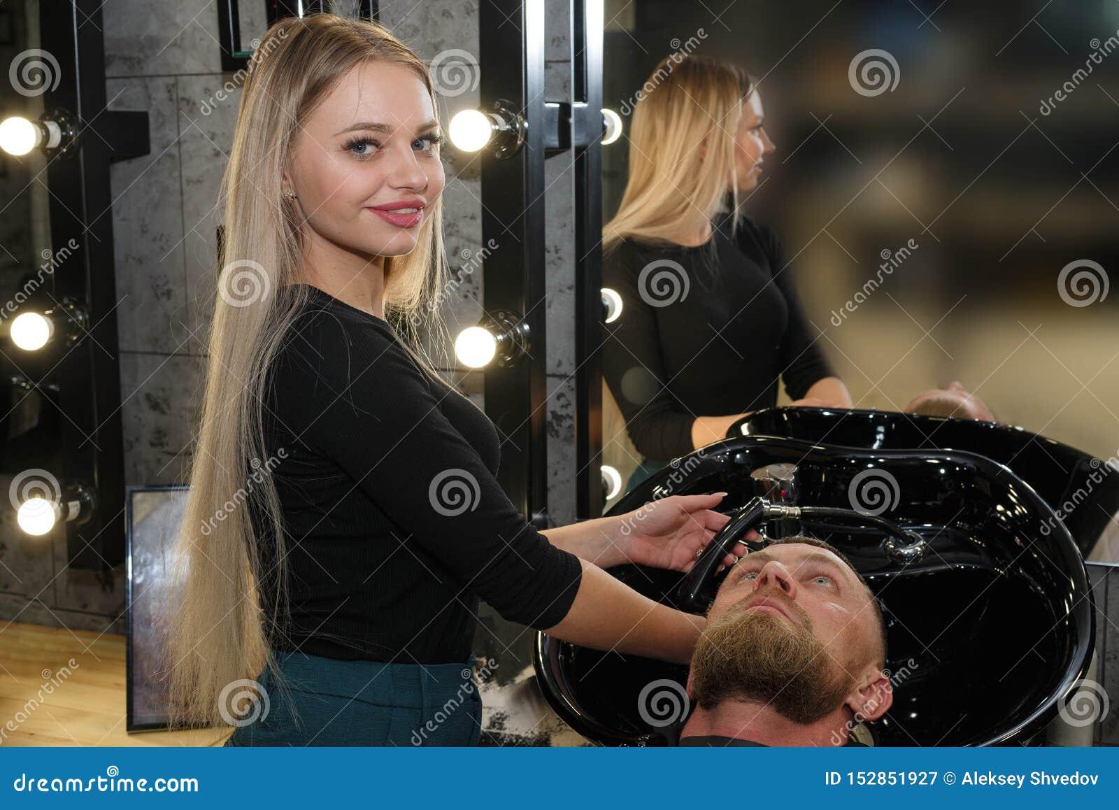 Capelli del ` s del cliente di lavaggio del parrucchiere nel negozio di barbiere