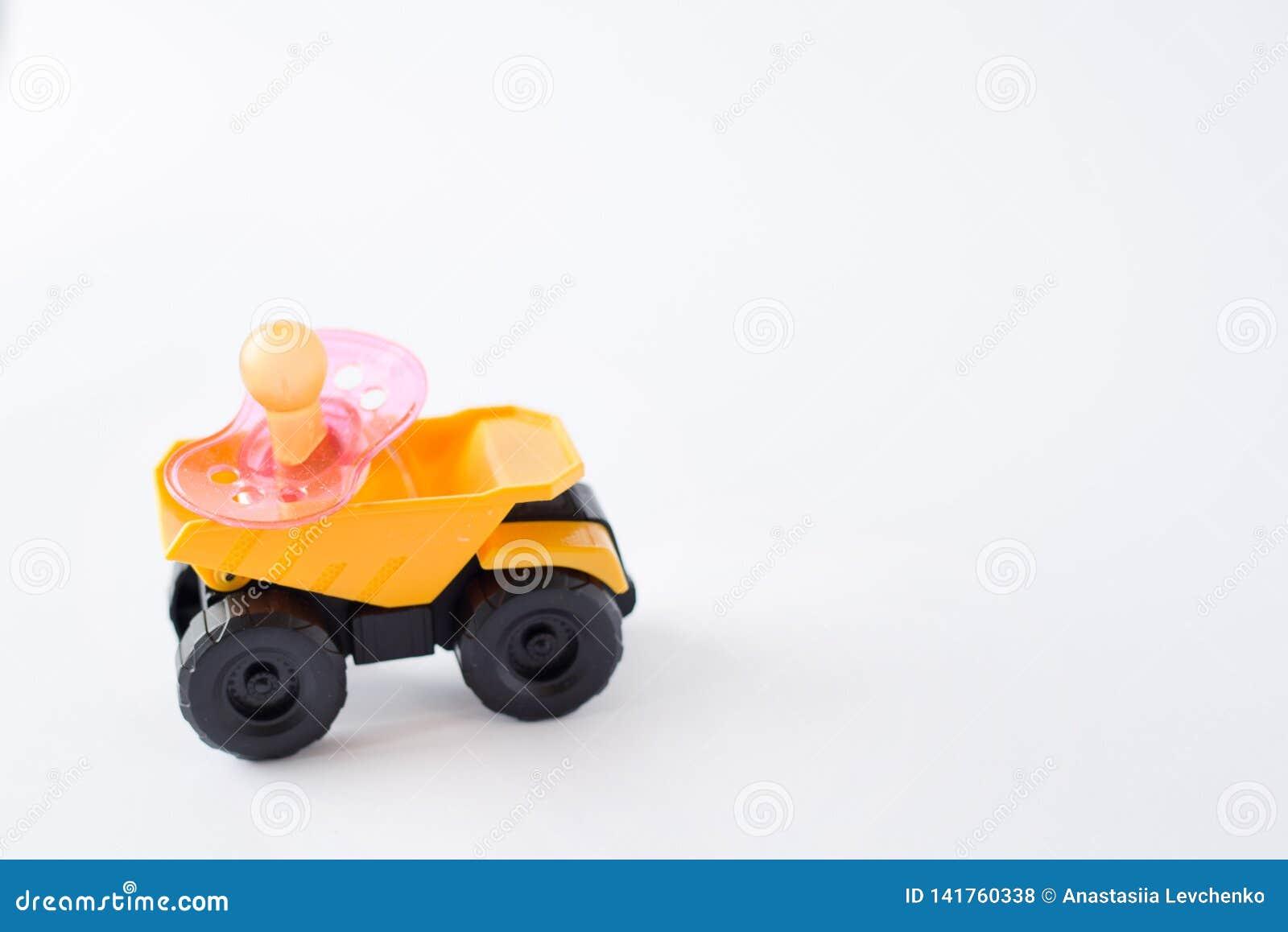Capezzolo della tettarella del bambino rosa sull automobile gialla isolata su fondo bianco Posto per testo Copi lo spazio
