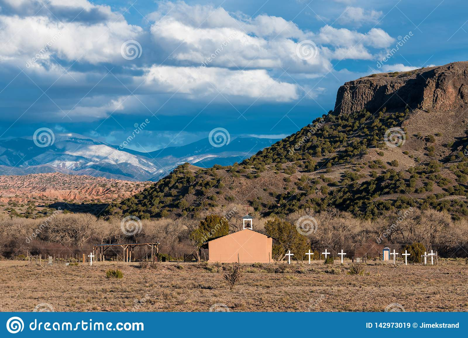 An old Spanish mission style church with a row of white crosses in a southwestern landscape of mesas, badlands, and mountains
