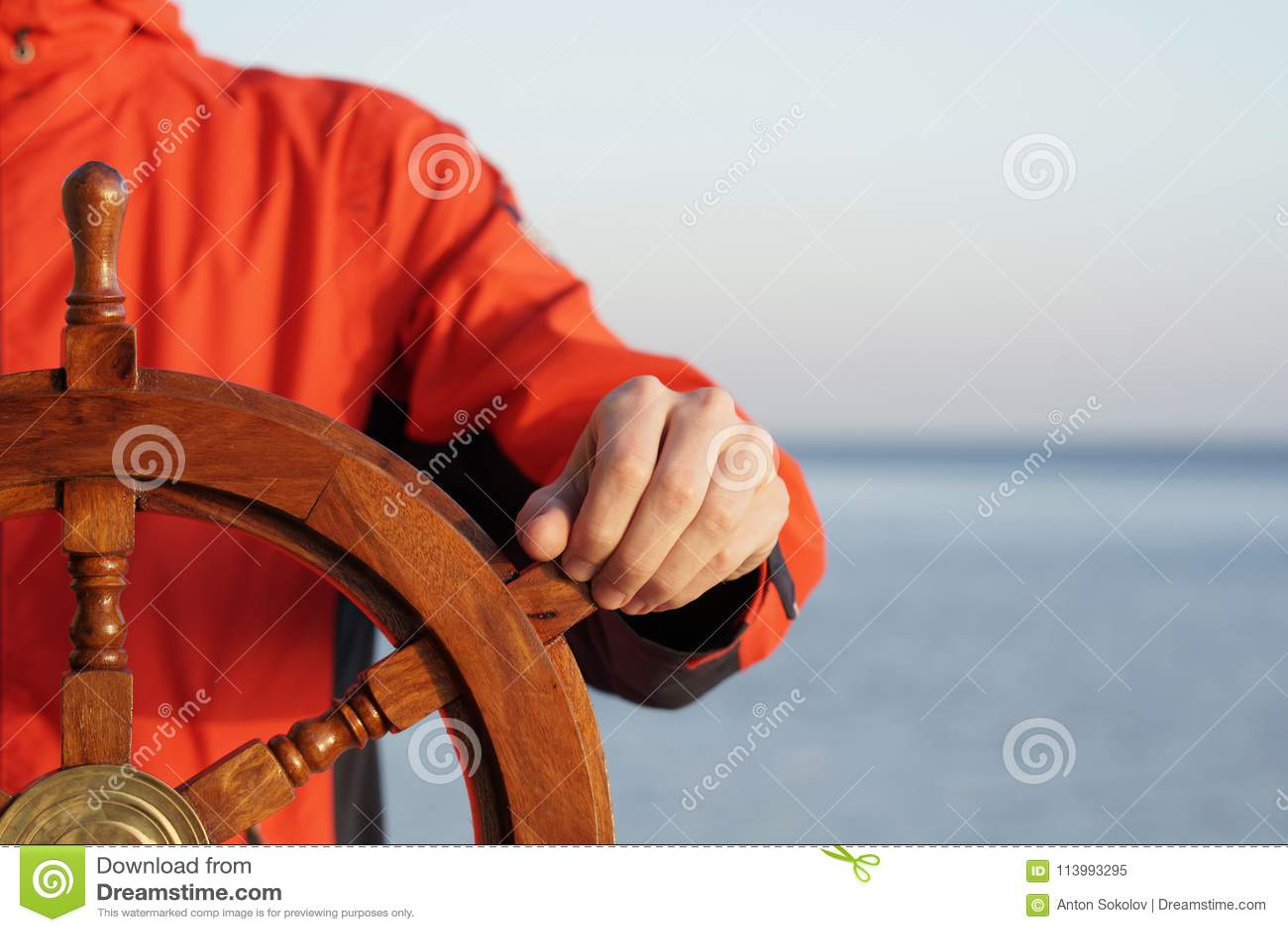 Capitaine tenant la main sur le gouvernail de direction de bateau