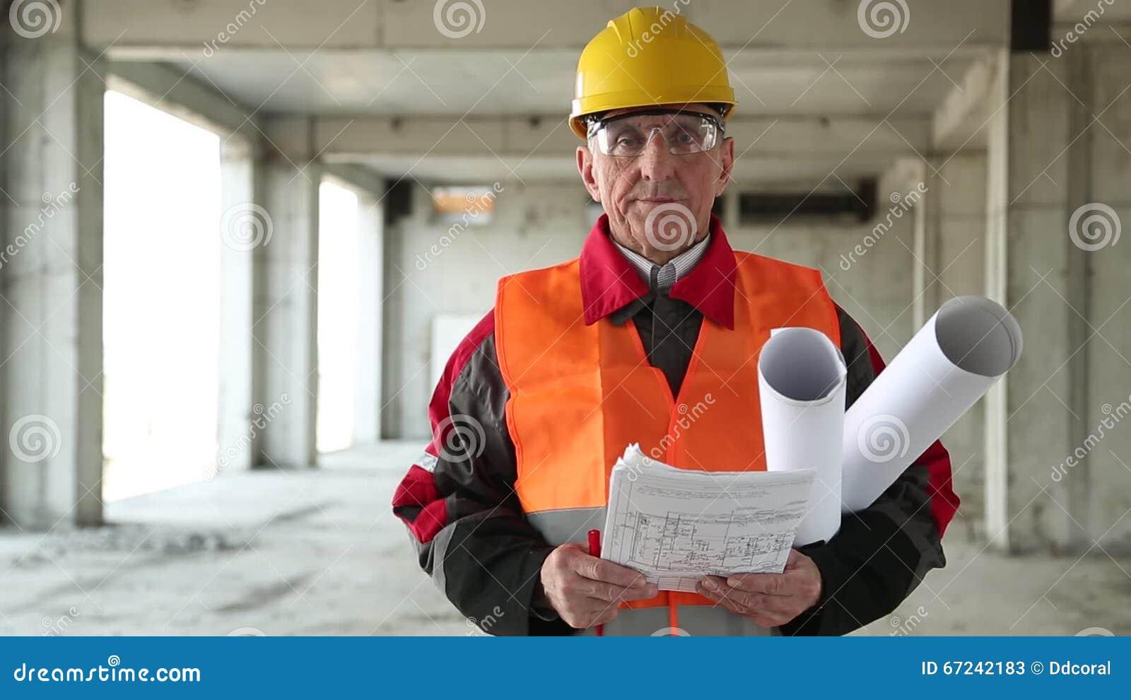 Capo Ufficio Disegno : Capo cantiere con i disegni della costruzione al sito di progetto