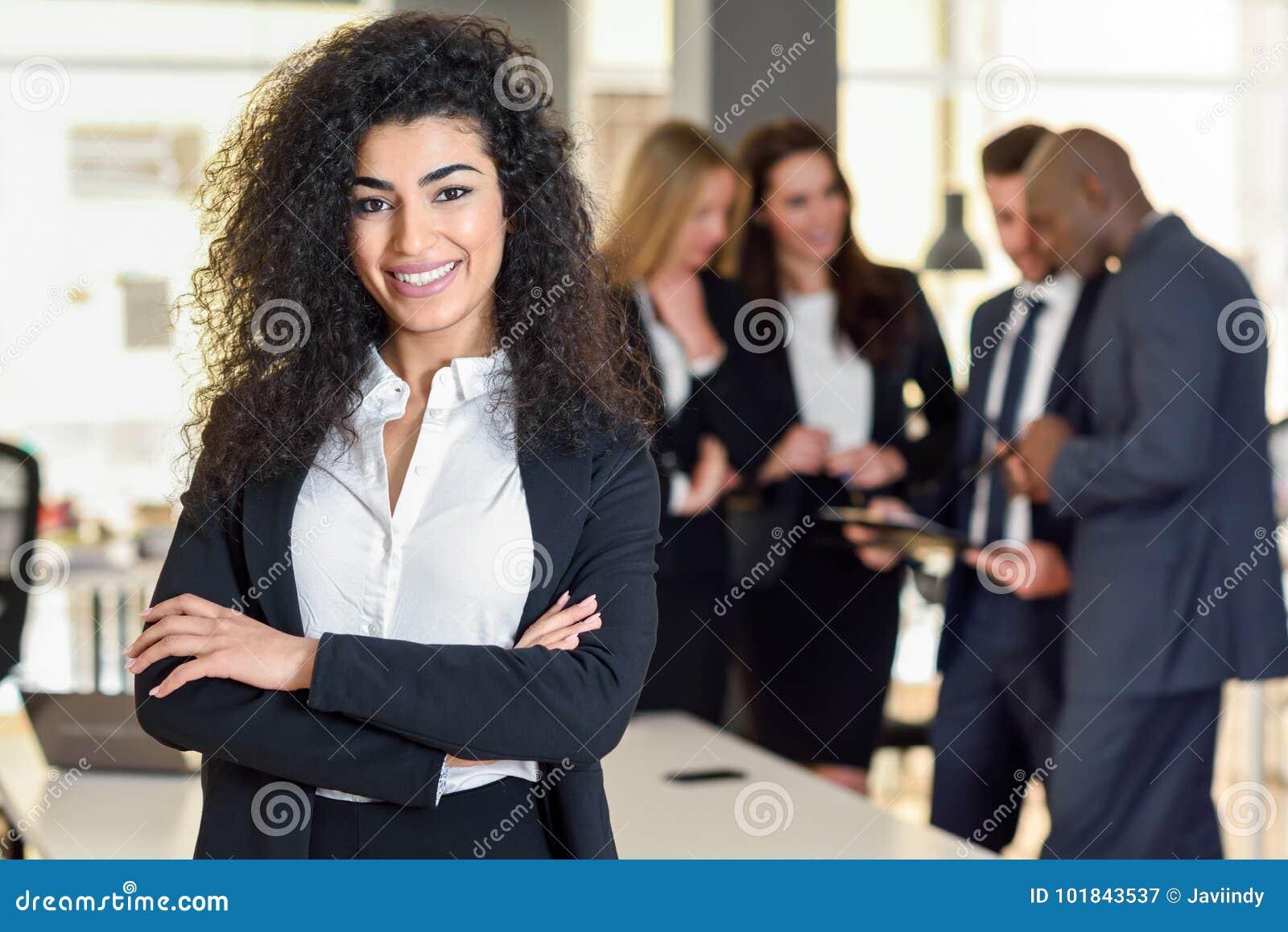 Capo della donna di affari in ufficio moderno con il workin delle persone di affari
