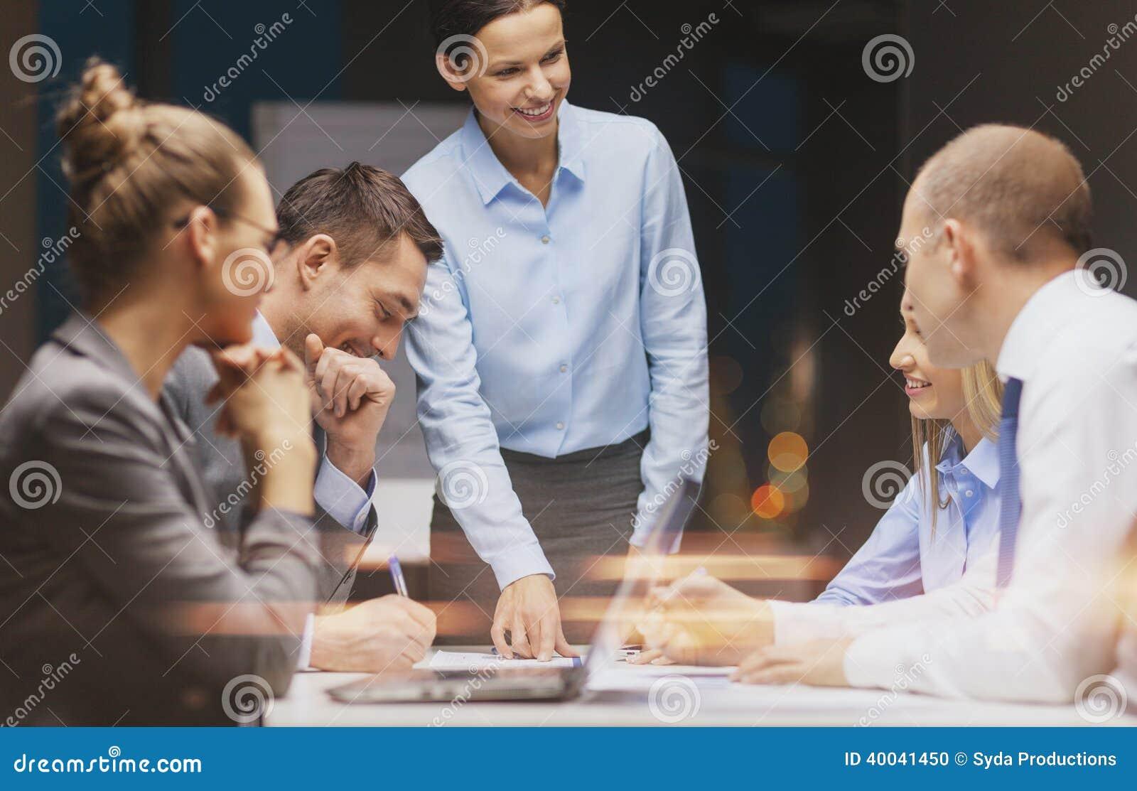 Capo femminile sorridente che parla con gruppo di affari