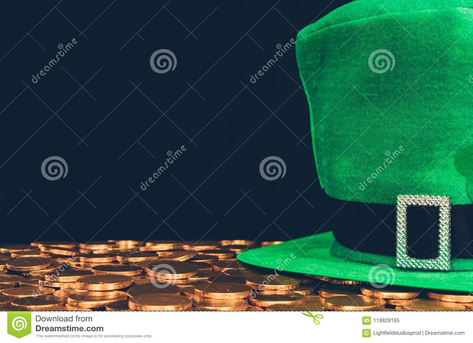 Cappello verde sulle monete dorate isolate sul nero, concetto di giorno dei patricks della st