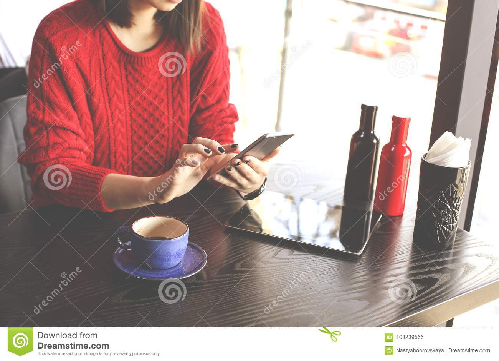 Cappuccino bebendo da jovem mulher feliz, latte, macchiato, chá, usando o tablet pc e falando no telefone em uma cafetaria/vagabu