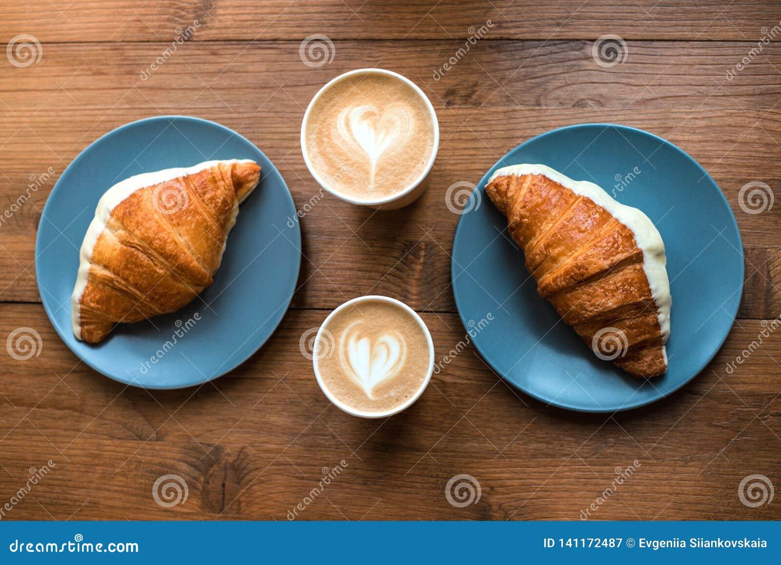 Cappuccino croissants na drewnianym tle i sztuka